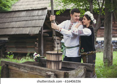 Inlove young couple dressed in traditional romanian costume near a fountain of wood