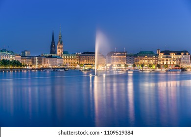 The Inner Alster Lake (German: Binnenalster) in Hamburg, Germany. View of the inner city at dusk with the fountain reflecting in the water.