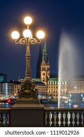 The Inner Alster Lake (German: Binnenalster) in Hamburg, Germany. View of the city at night with the fountain reflecting in the water and the Renaissance Revival Lombard Bridge (Lombardsbruecke).