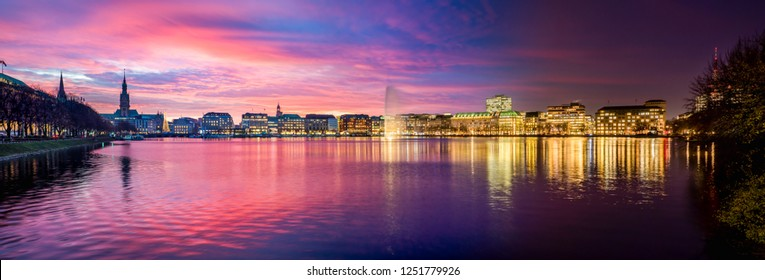 The Inner Alster Lake (German: Binnenalster) in Hamburg, Germany. Panoramic view of the inner city at dusk with the fountain and the city lights reflecting in the water.