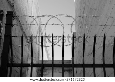 An Inner City Fence With Sharpened Vertical Bars Barbed Wire And Concertina Conveys The