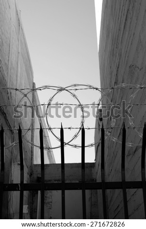 An Inner City Fence With Sharpened Vertical Bars Barbed Wire And Concertina Conveys The Message Keep Out Monochrome Image
