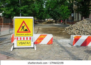 Inner city road closed by stone roadblocks during reconstruction. Yellow roadsign with the words in Ukrainian mean ROAD WORK, ATTENTION. City street under reconstruction