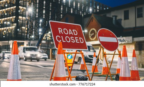 Inner city road closed by orange roadblock cones during night maintenance