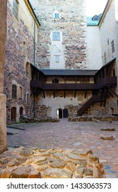 The inner courtyard has stone walls and wooden galleries of the historical medieval castle-fortress Abo in the city of Turku in Finland on a summer day.