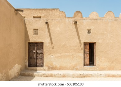 The inner courtyard of a restored traditional old Arabian building in strong sunlight with shadows from wooden gutters and carved wooden doors and window lattices for ventilation.