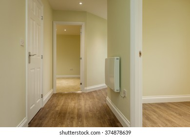 Inner hall within residential property with wall mounted radiator and open doors leading to further rooms