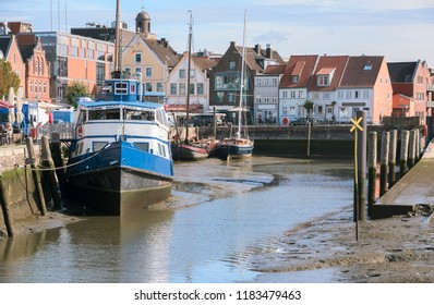 Inner harbor at low tide in the old town of Husum with boats on the mudflat and houses on a sunny day, north sea coast in germany, selected focus