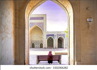 Inner yard of ancient Kalyan Mosque, part of the Po-i-Kalyan Complex. Bukhara, Uzbekistan. A woman in a headscarf sitting on the bench.