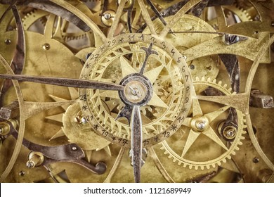 Innerworks of an antique clock with gear wheels and hour and minute hand