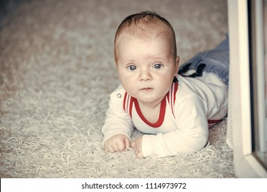Innocence, beauty, purity. Baby with blue eyes on adorable face. Infant crawl on floor carpet. Child development concept. Childhood, infancy, newborn.
