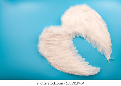 Innocence and purity, Christian mythology and innocent celestial creatures concept with guardian angel wings made of white feathers isolated on blue background with copy space