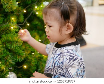 Innocent Asian baby girl holding on / touching a string light on a Christmas tree with no fear of a risk of being electrocuted