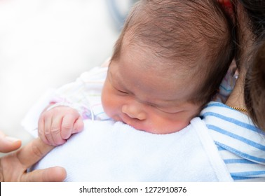 Innocent baby,Happy Asian baby girl sleeping on mother shoulder,Portrait of a loving mother hold baby to burp after breastding,Mother holding one month old baby girl on her shoulder,carrying baby burp
