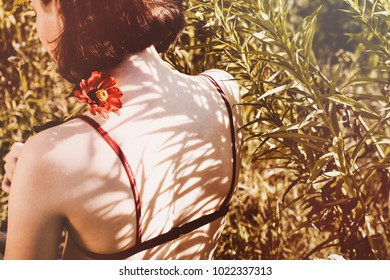 Innocent girl with red flower. Woman in green field. Symbol of innocence, passion. Lingerie, bra. Short hair. Shadow and light. Sunlight and sunny day. Sadness and silence.