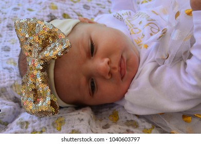 Innocent infant baby girl laying on a blanket looking down