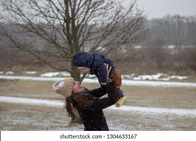 innocent love between young smiling mother and her beautiful babyboy son looking eye to eye holding baby up in winter