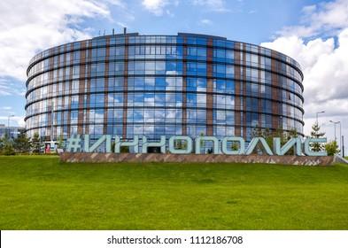 "Innopolis, Russia - June 11, 2018: Modern building in It-village in Kazan district.  Inscription ""Innopolis"" in big letters on the ground. Innopolis city in Republic of Tatarstan"