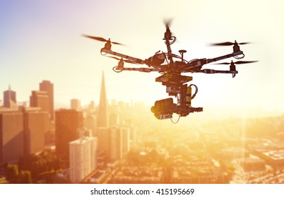 Innovation photography concept. Silhouette drone Flying over San-Francisco city on blurred background. Heavy lift drone photographing city at sunset.
