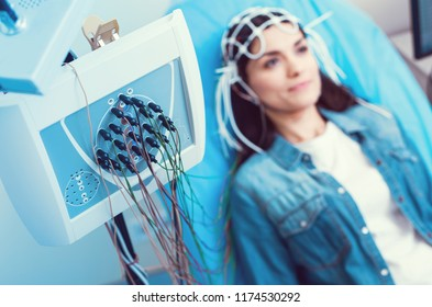 Innovative approach. Selective focus on an electroencephalography machine with node with a brunette lady getting her brain analyzed at a lab.