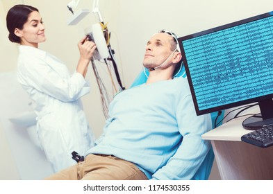 Innovative approach. Selective focus on a PC displaying brain waves on a male patient lying on an examination couch and undergoing electroencephalography procedure.