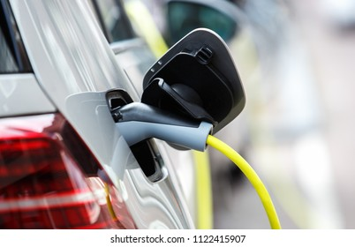 Innovative electric hybrid car charging batteries with electricity through power cable on parking.Clean eco vehicle with cheap electrical engine.Care about environment.Electrical cars charging