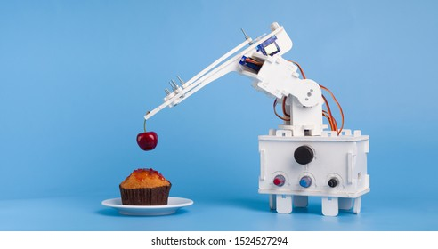 Innovative kitchen technology. Robot cooking dessert, decorating sweet cupcake with fresh cherry, blue panorama background