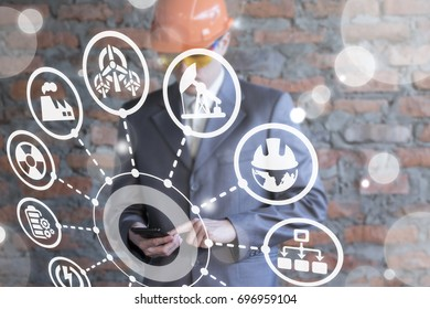 Innovative Mobile Information Technologies in Energy Production. Smart Industry 4.0 concept. Industrial business man working on smartphone on a virtual graphical user interface.