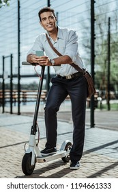 Innovative transport. Glad optimistic guy leaning on electric scooter and holding phone