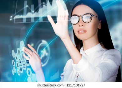 Innovative use of technology in business concept. A young business woman is operating inside an augmented reality, holographic space, monitoring data and analytics with a virtual 3D environment