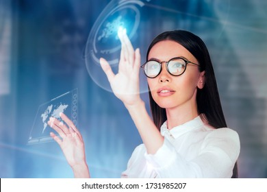 Innovative use of technology in business concept. A young business woman is operating inside an augmented reality, holographic space, monitoring data and analytics with a virtual 3D monitor