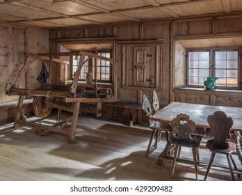 INNSBRUCK, AUSTRIA - 13 MAY 2016: Tiroler Volkskunstmuseum (Museum of Tyrolean Regional Heritage). The interior of the room in traditional tyrolean peasant house - wooden table, loom, weaving machine