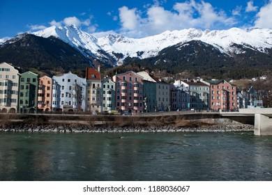 INNSBRUCK, AUSTRIA - January 08, 2018:  view of the historic city center with colorful houses along Inn river and famous Austrian mountain summits in the background.