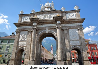 INNSBRUCK, AUSTRIA - JULY 2, 2018: Triumphal Arch (Triumphpforte) located on street Maria Theresien Strasse, with the bell tower of Servite Monastery (Servitenkloster) in the background