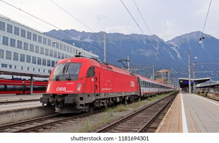Innsbruck / Austria - July 28 2018: A train of the ÖBB with a red electric locomotive and ÖBB passengers coaches at the railway station of Innsbruck with mountains of the Alps at the background