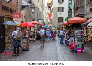 Innsbruck, Austria - June 8, 2018: People in the historical city centre with cafes and souvenir shops. Innsbruck is the capital city of Tyrol in western Austria.