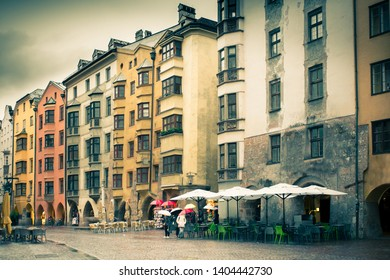 Innsbruck Austria rainy day street scene with old architecture, unrecognizable people and umbrellas,