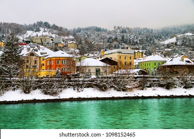 Innsbruck, Austria. View of the Inn river in winter in Innsbruck, Austria during the early morning, trees and mountains at the background. Various hotels and restaurants