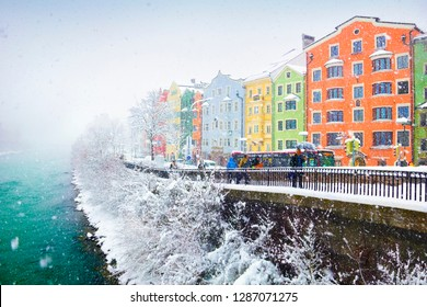 INNSBRUCK/AUSTRIA - JAN 11. Snowy weather, colorful houses, naked trees covered with snow and few people walk alongside the Inn river on January 11, 2019 in Innsbruck, Tyrol (Tirol), Austria, Europe