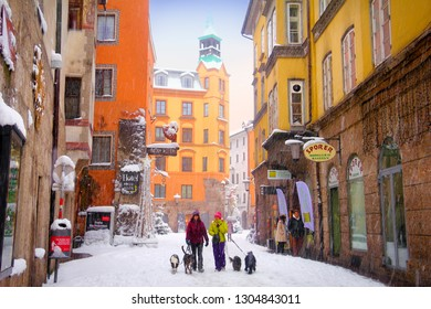 INNSBRUCK/AUSTRIA - JAN 11. Snowy weather, two unidentified women walking with dogs, traditional city houses and street full of snow on January 11, 2019 in Innsbruck, Tyrol (Tirol), Austria, Europe