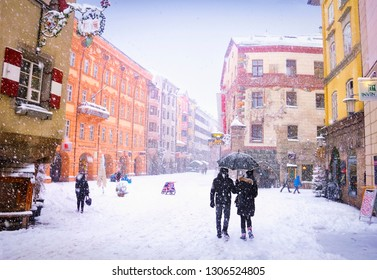 INNSBRUCK/AUSTRIA - JAN 11. Snowy weather, couple of people walking under an umbrella, traditional city houses and street full of snow on January 11, 2019 in Innsbruck, Tyrol (Tirol), Austria, Europe,