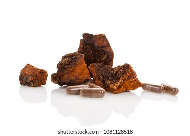 Inonotus obliquus, chaga chunks and supplement in gel capsules isolated on white background. Medicinal mushroom.