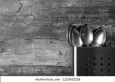 Inox stand with cutlery spoon and forks on a wooden board in monochrome style
