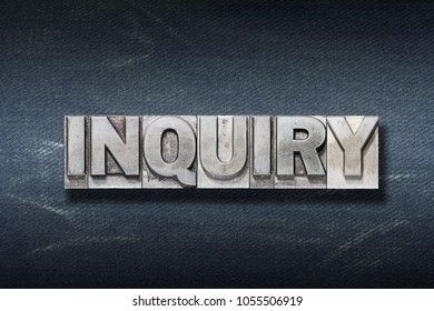 inquiry word made from metallic letterpress on dark jeans background