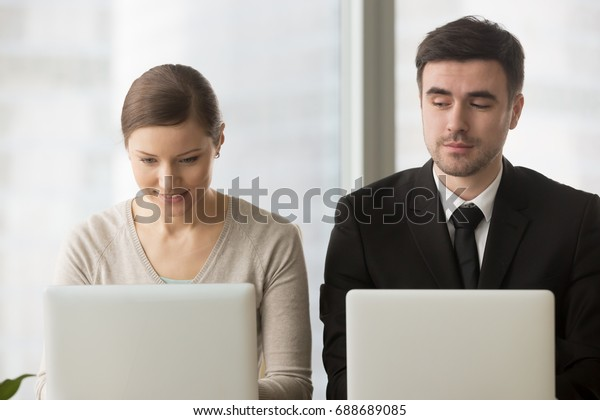 Inquisitive curious businessman with bad manners sneakly looking at laptop screen of businesswoman trying to steal idea of competitor, copying work at corporate exam, gathering information on rival