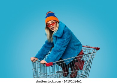 Insane female dapper in bright outfit looking at camera while riding trolley during shopping against blue background