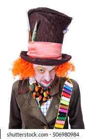 The insane funny Hatter: a man dressed in a velour brown frock coat, cylinder hat and the bow tie grimacing and is playing the fool - close-up portrait, isolated