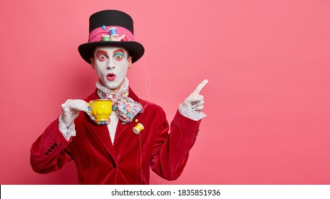 Insane mysterious unique character obsessed with tea drinking dressed fashionably has big hat points at upper right corner against pink background. Mad hatter demonstrates direction on empty space