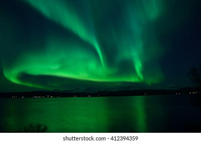 insanely strong aurora borealis over arctic fjord and mountain landscape