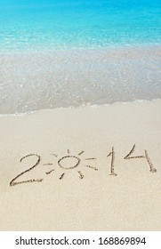 inscription 2014 on sea sand beach with the sun rays against wave foam and sky - vacation concept